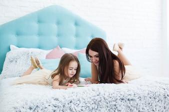 Joven mujer mira cómo su niño pinta acostado en la cama