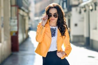 Joven mujer morena con gafas de sol en el fondo urbano