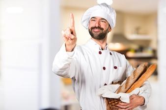 Joven panadero sosteniendo un poco de pan tocando la pantalla transparente en la cocina