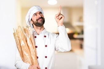 Joven panadero sosteniendo un poco de pan y apuntando hacia arriba en la cocina