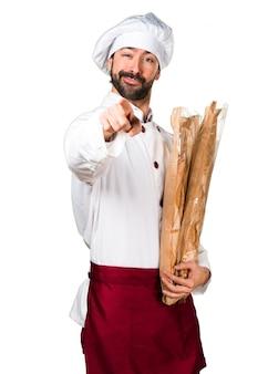 Joven panadero sosteniendo un poco de pan y apuntando hacia el frente