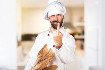 Joven panadero sosteniendo un poco de pan y haciendo gesto de cuerno en la cocina