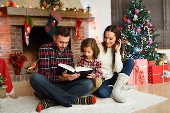 Joven pareja leyendo un libro con una niña en su sala de estar decoradas para la navidad