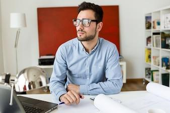 Joven trabajador de oficina masculino en el lugar de trabajo