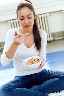 Joven y bella mujer comiendo cereales en casa.