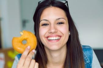 Joven y bella mujer comiendo donas en casa.