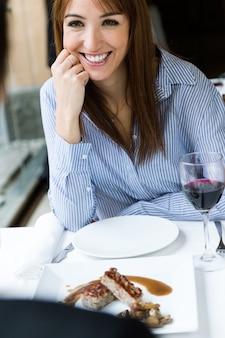 Joven y bella mujer comiendo pastel de carne en el restaurante.