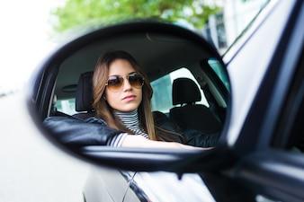 Joven y bella mujer conduciendo su coche.