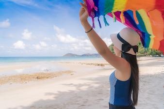 Joven y bella mujer en la playa con la bufanda