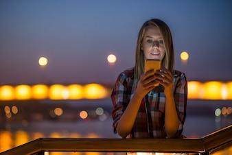 Joven y bella mujer hablando por teléfono móvil en la ciudad de la noche.