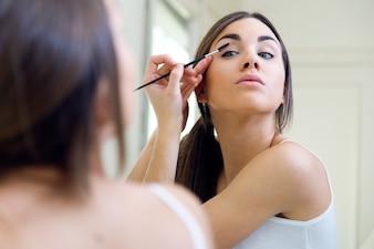 Joven y bella mujer haciendo maquillaje cerca de espejo.