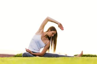 Joven y bella mujer haciendo yoga en la calle.