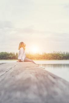 Joven y bella mujer inconformista que se sienta en el lago se relaja con