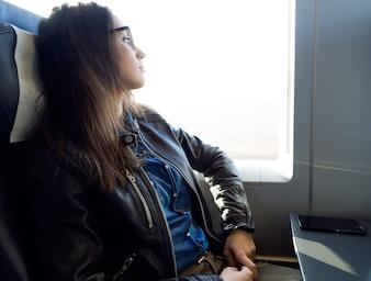 Joven y bella mujer que viaja en tren.