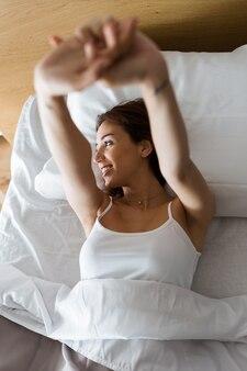 Joven y bella mujer se extiende en la cama después de despertar.