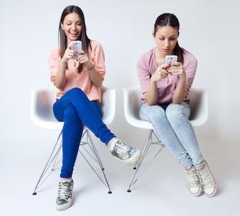 Joven y bella mujer utilizando su teléfono móvil en casa.