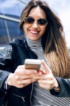Joven y bella mujer utilizando su teléfono móvil en el coche.