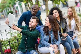 Jóvenes multiétnicos tomando selfie juntos en backgr urbana