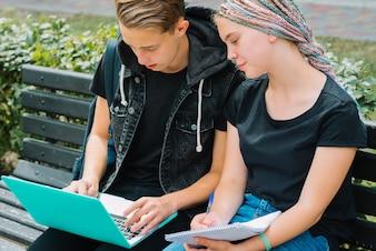 Jóvenes que estudian con la computadora portátil