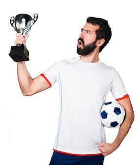 Jugador de fútbol afortunado con un balón de fútbol