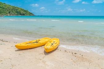 Kayaks amarillas en la playa de arena blanca