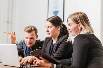 La gente sentada en el escritorio de trabajo en la computadora portátil