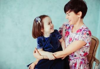 La madre con la hija que abraza y que se sienta en la silla