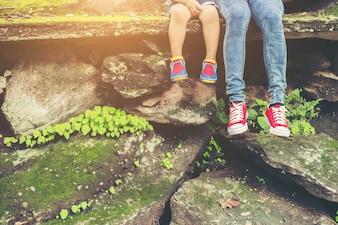 La madre y sus pequeños pies hijo sentado en el acantilado.