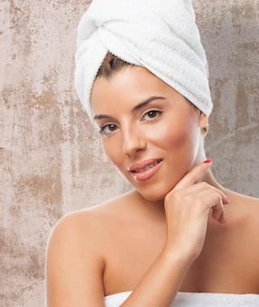 La muchacha sonriente en una toalla blanca con la mano en la barbilla