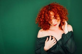 La mujer con el pelo rojo rizado se coloca con los hombros desnudos antes de la pared verde