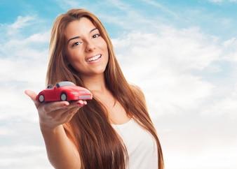 La mujer muestra el coche de juguete.