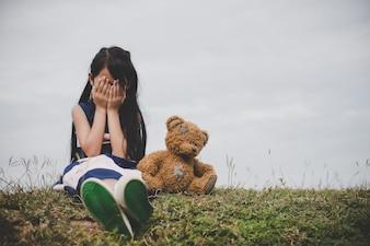 La niña que se sienta con su oso trastornado en el campo de los prados.