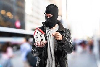 Ladrón sosteniendo una pequeña casa en fondo unfocused