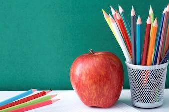 Lápices de colores con manzana en un cuaderno