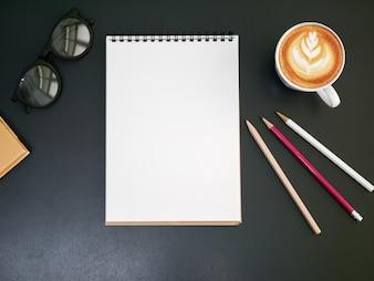Lápiz de bloc de notas en blanco sobre el escritorio de la oficina con taza de café, vista superior