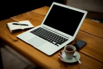 Ordenador portátil con café en escritorio de oficina