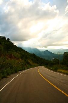Largo camino recto ir a la montaña y el cielo