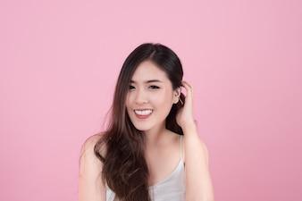 Largo pelo asiática joven sonrisa hermosa mujer y tocar su rostro, aislado sobre fondo de color rosa. maquillaje natural, terapia SPA, cuidado de la piel, cosmetología y cirugía plástica concepto