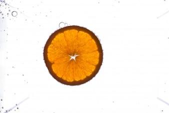 Las burbujas cubren la rebanada de naranja fresco que flota en el agua