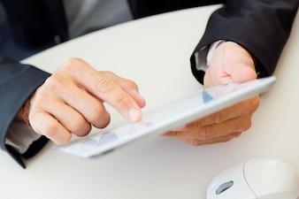 Las manos del hombre usando una tableta