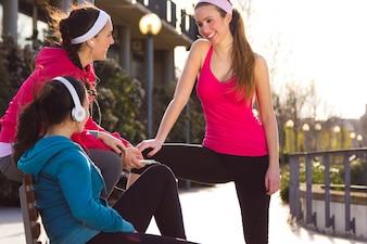 Las mujeres se sientan en banco en ropa deportiva