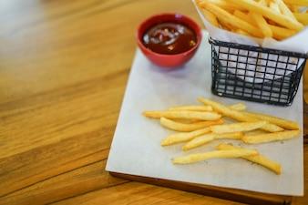 Las patatas fritas en la mesa de madera