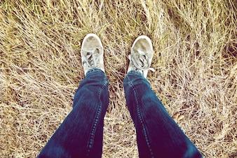 Las piernas adolescentes en hierba.