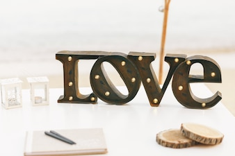 Letras de acero oscuro LOVE with lamps stands on white table
