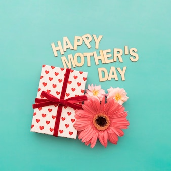 Lettering  happy mother's day , caja de regalos y flores de cerca
