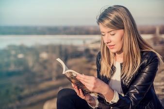 Leyendo su libro favorito. Joven y bella mujer leyendo el libro y sonriendo mientras está sentado al aire libre, paisaje en el fondo. Lectura de un concepto de libro