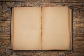 Libro antiguo abierto en una mesa de madera visto desde arriba