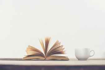 Libro pasando páginas y una taza