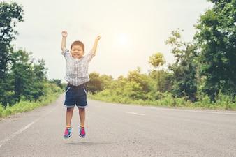 Lindo niño asiático que salta en el camino.