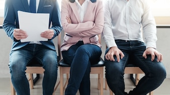 Línea de jóvenes empresarios sentados esperando su turno para la entrevista.